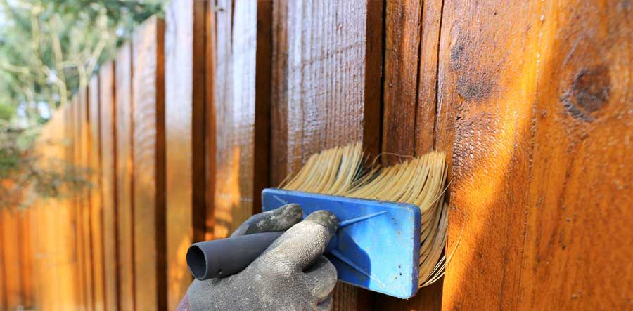 Board on Board Fence Being Stained